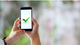 Man holding mobile phone displaying green checkmark [Image by creator  from insideARM]